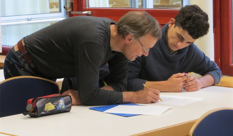 Über das Gedicht gebeugt: Walle Sayer bespricht sich mit einem Schüler  GB-Foto: gb