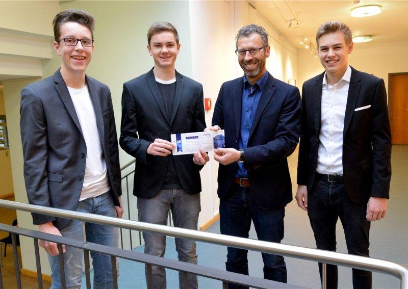Felix Schwer (von links), Armin Schick und Yannick Christ (rechts) übergeben OB Thomas Sprißler (Zweiter von rechts) eine Aktie  GB-Foto: Holom