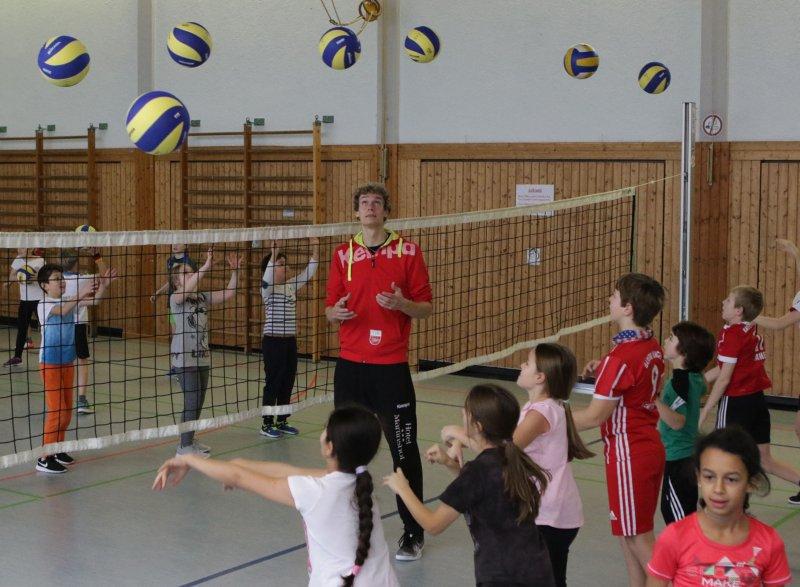 Lars Wilmsen bringt den Kindern bei, wie sie den Ball über das Netz pritschen  GB-Foto: Bäuerle